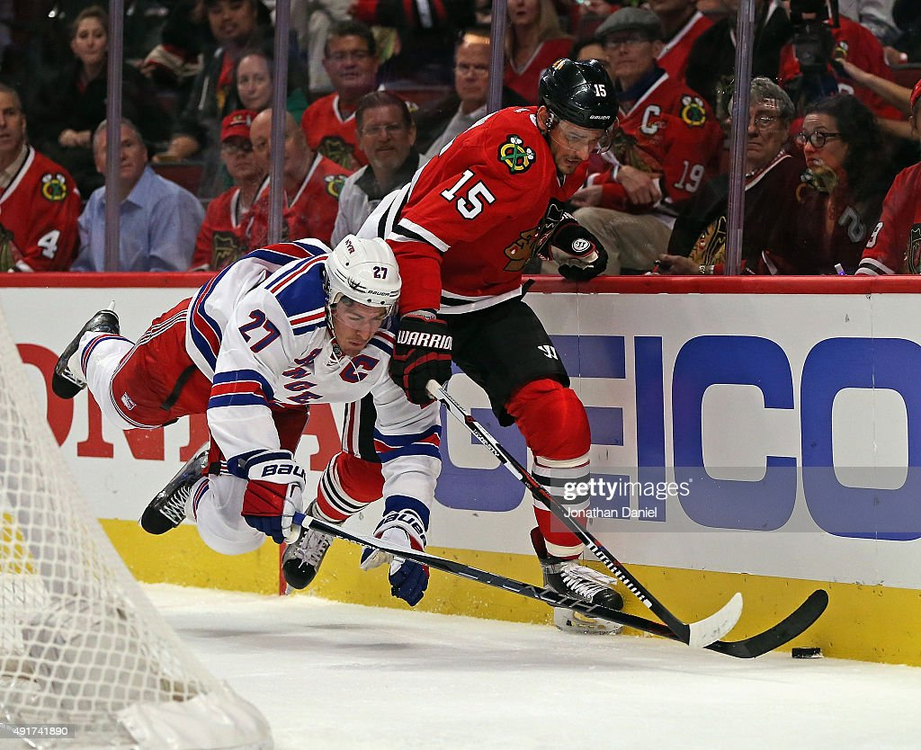 Ryan McDonagh of the New York Rangers go airborne as he battle for the puck with Artem Anisimov of the Chicago Blackhawks during an NHL game at the...