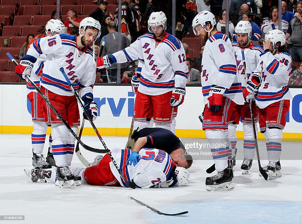 Ryan McDonagh #27 of the New York Rangers is tended to by a team trainer after being hit by a puck as his teammates look on during the game against the Anaheim Ducks skates away on March 16, 2016 at Honda Center in Anaheim, California.