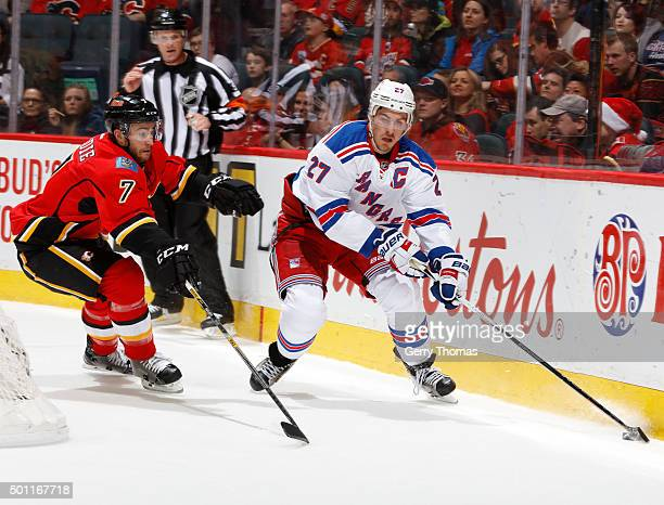 Ryan Mcdonagh of the New York Rangers protects the puck from TJ Brodie of the Calgary Flames at Scotiabank Saddledome on December 12 2015 in Calgary...