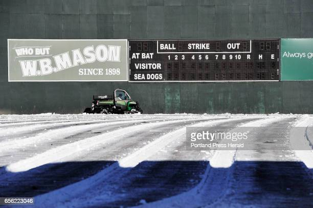 Ryan McGillivray of Sports Turf Specialties Inc spreads black sand over Hadlock Field Saturday March 18 2017 The black sand absorbs the heat from the...