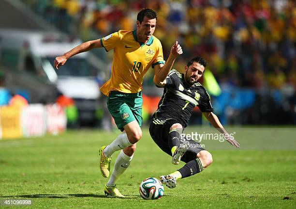 Ryan McGowan of Australia is challenged by David Villa of Spain during the 2014 FIFA World Cup Brazil Group B match between Australia and Spain at...