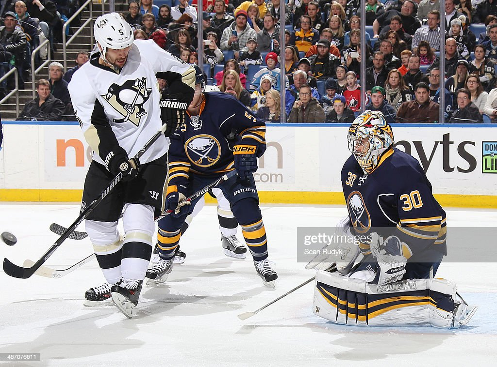 Ryan Miler #30 and Chad Ruhwedel #5 of the Buffalo Sabres keep a close eye on a shot as Deryk Engelland #5 of the Pittsburgh Penguins looks for a rebound at First Niagara Center on February 5, 2014 in Buffalo, New York. Pittsburgh defeated Buffalo 5-1. (Photo by Sean Rudyk/Getty Images).