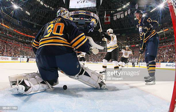 Ryan Miller and Tyler Myers of the Buffalo Sabres watch as the Boston Bruins celebrate a secondperiod goal scored by Mark Recchi in Game One of the...