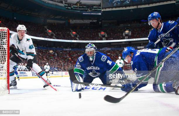 Ryan Miller Evan McEneny and Ben Hutton of the Vancouver Canucks watch a loose puck against Tomas Hertl of the San Jose Sharks during their NHL game...