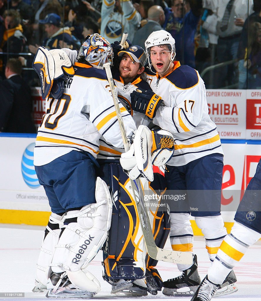 Ryan Miller #30, Jhonas Enroth #1, and Marc-Andre Gragnani #17 of the Buffalo Sabres celebrate an overtime win against the Philadelphia Flyers at HSBC Arena on March 8, 2011 in Buffalo, New York, securing the Sabres a spot in the playoffs.