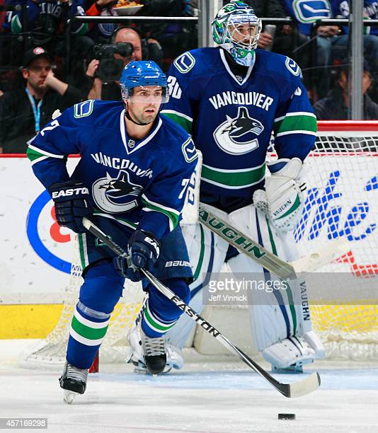 Ryan Miller looks on as Dan Hamhuis of the Vancouver Canucks skates up ice with the puck during their NHL game against the Edmonton Oilers at Rogers...