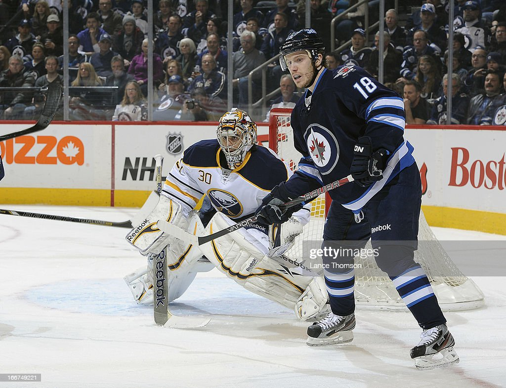 Ryan Miller #30 of the Buffalo Sabres and Bryan Little #18 of the Winnipeg Jets keep an eye on the play during first period action at the MTS Centre on April 9, 2013 in Winnipeg, Manitoba, Canada. The Jets defeated the Sabres 4-1.