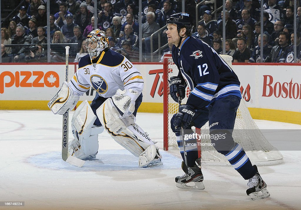 Ryan Miller #30 of the Buffalo Sabres and Olli Jokinen #12 of the Winnipeg Jets keep an eye on the play during first period action at the MTS Centre on April 9, 2013 in Winnipeg, Manitoba, Canada. The Jets defeated the Sabres 4-1.