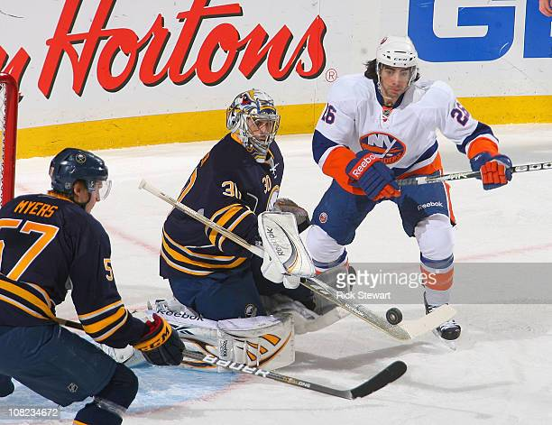 Ryan Miller of the Buffalo Sabres flips the puck to Tyler Myers and away from Matt Moulson of the New York Islanders at HSBC Arena on January 21 2011...