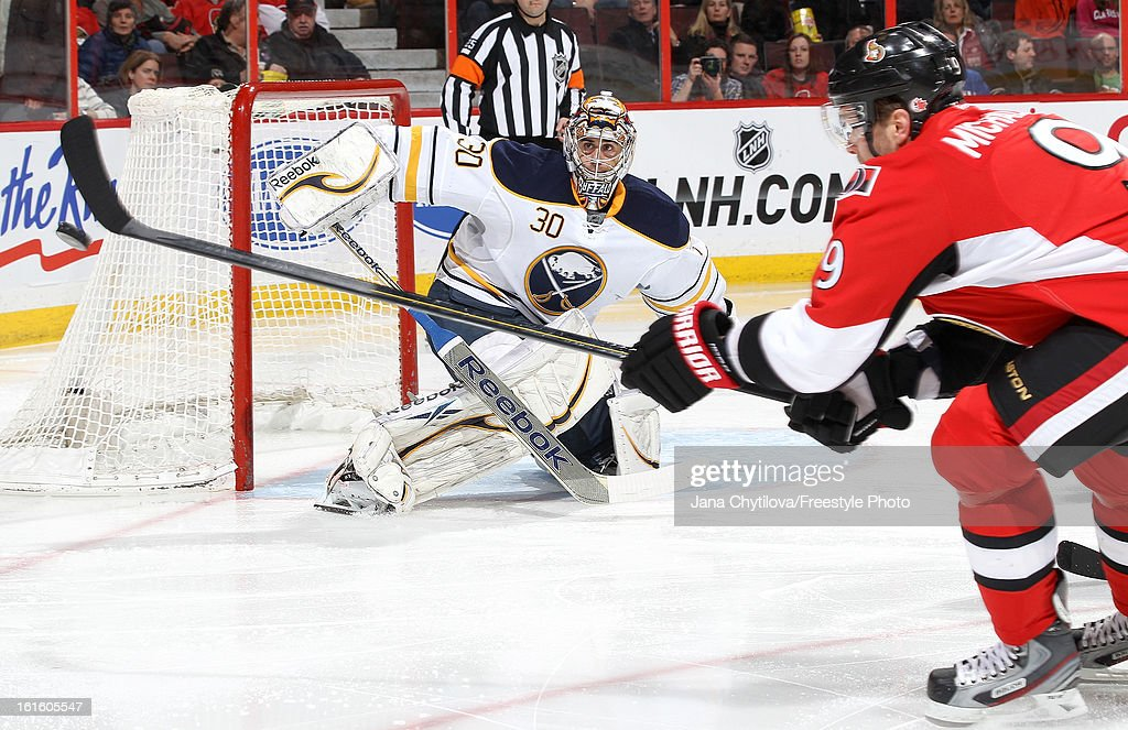 Ryan Miller #30 of the Buffalo Sabres keeps his eye on the puck as Milan Michalek #9 of the Ottawa Senators tries to tip the puck, during an NHL game at Scotiabank Place on February 12, 2013 in Ottawa, Ontario, Canada.