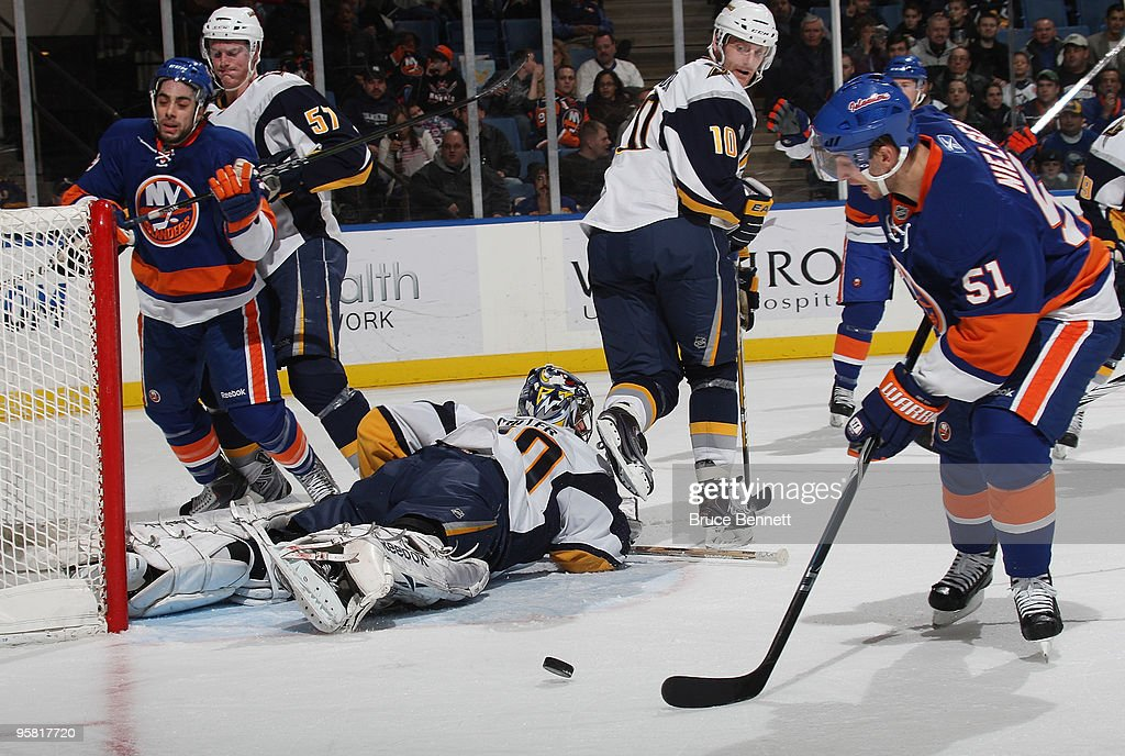 Ryan Miller of the Buffalo Sabres lies on the ice prior to making a save against Frans Nielsen of the New York Islanders at the Nassau Coliseum on...