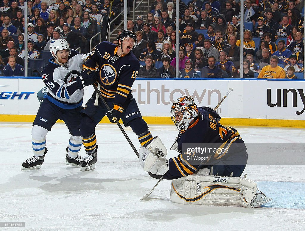 Ryan Miller #30 of the Buffalo Sabres makes a glove save as teammate <a gi-track='captionPersonalityLinkClicked' href=/galleries/search?phrase=Christian+Ehrhoff&family=editorial&specificpeople=214788 ng-click='$event.stopPropagation()'>Christian Ehrhoff</a> #10 ties up Jim Slater #19 of the Winnipeg Jets on February 19, 2013 at the First Niagara Center in Buffalo, New York.