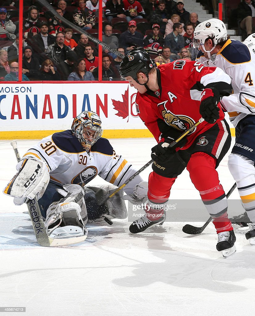 Ryan Miller #30 of the Buffalo Sabres makes a save against Chris Neil #25 of the Ottawa Senators with support from teammate Jamie McBain #4 at Canadian Tire Centre on December 12, 2013 in Ottawa, Ontario, Canada.