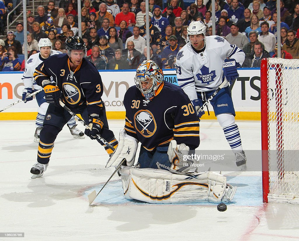 Ryan Miller #30 of the Buffalo Sabres makes a save in front of teammate <a gi-track='captionPersonalityLinkClicked' href=/galleries/search?phrase=Jordan+Leopold&family=editorial&specificpeople=201885 ng-click='$event.stopPropagation()'>Jordan Leopold</a> #3 and <a gi-track='captionPersonalityLinkClicked' href=/galleries/search?phrase=Joffrey+Lupul&family=editorial&specificpeople=206995 ng-click='$event.stopPropagation()'>Joffrey Lupul</a> #19 of the Toronto Maple Leafs at First Niagara Center on December 16, 2011 in Buffalo, New York.