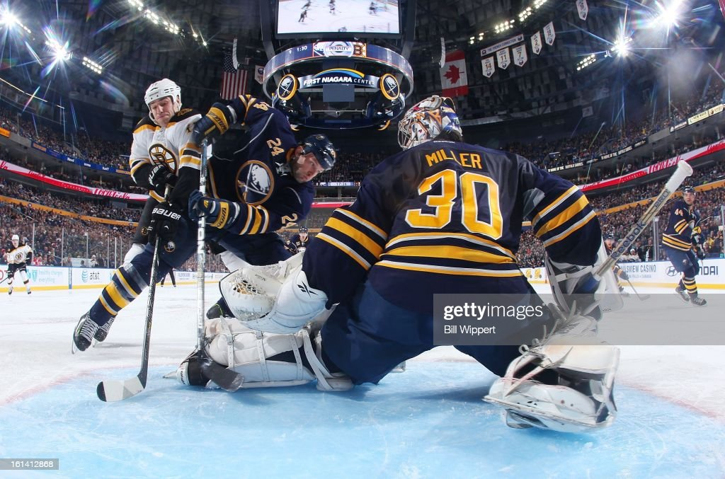 Ryan Miller #30 of the Buffalo Sabres makes a save in front of teammate <a gi-track='captionPersonalityLinkClicked' href=/galleries/search?phrase=Robyn+Regehr&family=editorial&specificpeople=171828 ng-click='$event.stopPropagation()'>Robyn Regehr</a> #24 and <a gi-track='captionPersonalityLinkClicked' href=/galleries/search?phrase=Milan+Lucic&family=editorial&specificpeople=537957 ng-click='$event.stopPropagation()'>Milan Lucic</a> #17 of the Boston Bruins on February 10, 2013 at the First Niagara Center in Buffalo, New York.