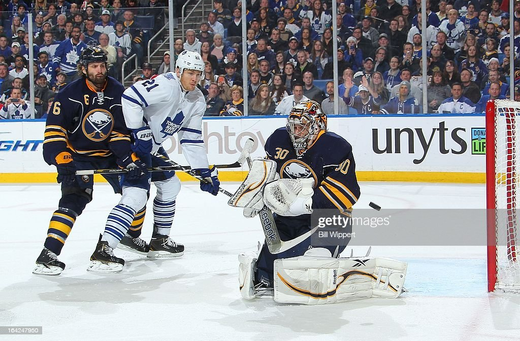 Ryan Miller #30 of the Buffalo Sabres makes a save in front of teammate Mike Weber #6 and James van Riemsdyk #21 of the Toronto Maple Leafs on March 21, 2013 at the First Niagara Center in Buffalo, New York.