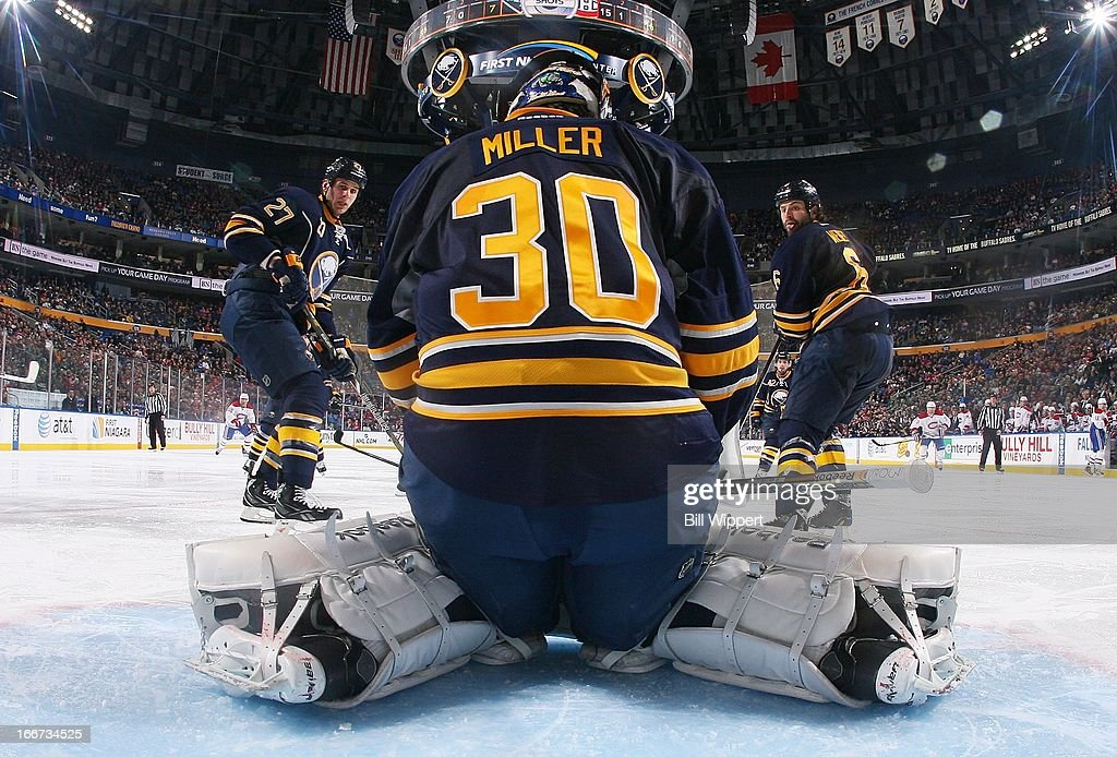 Ryan Miller #30 of the Buffalo Sabres makes a save in front of teammates Adam Pardy #27 and Mike Weber #6 against the Montreal Canadiens on April 11, 2013 at the First Niagara Center in Buffalo, New York.
