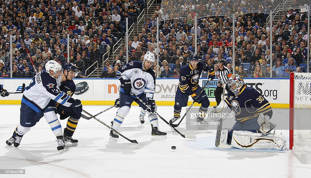 Ryan Miller #30 of the Buffalo Sabres makes a save on <a gi-track='captionPersonalityLinkClicked' href=/galleries/search?phrase=Kyle+Wellwood&family=editorial&specificpeople=577984 ng-click='$event.stopPropagation()'>Kyle Wellwood</a> #13 of the Winnipeg Jets as <a gi-track='captionPersonalityLinkClicked' href=/galleries/search?phrase=Tanner+Glass&family=editorial&specificpeople=4596666 ng-click='$event.stopPropagation()'>Tanner Glass</a> #15 of the Winnipeg Jets looks on with <a gi-track='captionPersonalityLinkClicked' href=/galleries/search?phrase=Tyler+Myers&family=editorial&specificpeople=4595080 ng-click='$event.stopPropagation()'>Tyler Myers</a> #57 and <a gi-track='captionPersonalityLinkClicked' href=/galleries/search?phrase=Andrej+Sekera&family=editorial&specificpeople=722503 ng-click='$event.stopPropagation()'>Andrej Sekera</a> #44 both of the Buffalo Sabres during their NHL game at First Niagara Center November 8, 2011 in Buffalo, New York.
