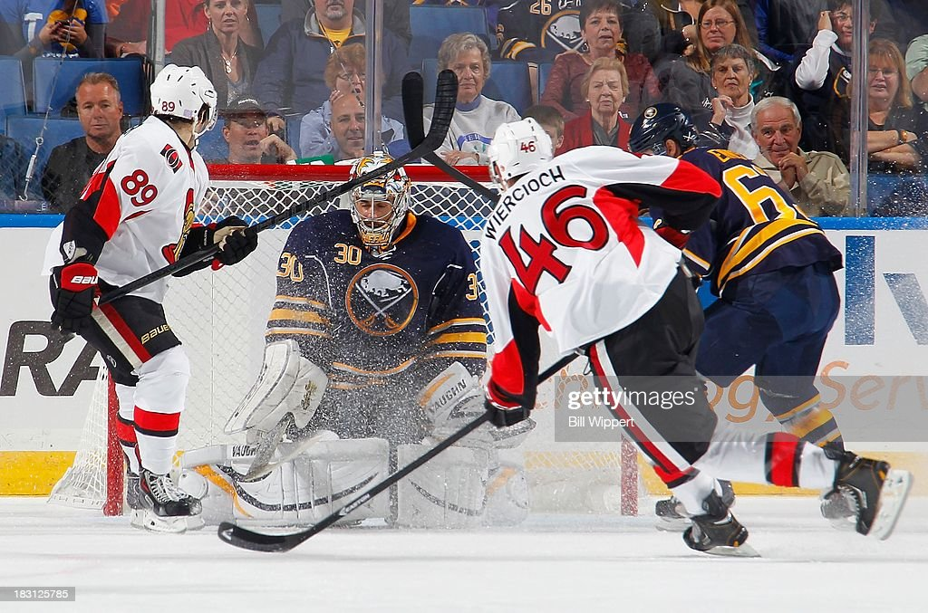 Ryan Miller #30 of the Buffalo Sabres makes a third-period save on a shot from <a gi-track='captionPersonalityLinkClicked' href=/galleries/search?phrase=Patrick+Wiercioch&family=editorial&specificpeople=5408887 ng-click='$event.stopPropagation()'>Patrick Wiercioch</a> #46 of the Ottawa Senators with <a gi-track='captionPersonalityLinkClicked' href=/galleries/search?phrase=Cory+Conacher&family=editorial&specificpeople=8312407 ng-click='$event.stopPropagation()'>Cory Conacher</a> #89 of the Senators alongside on October 4, 2013 at the First Niagara Center in Buffalo, New York.