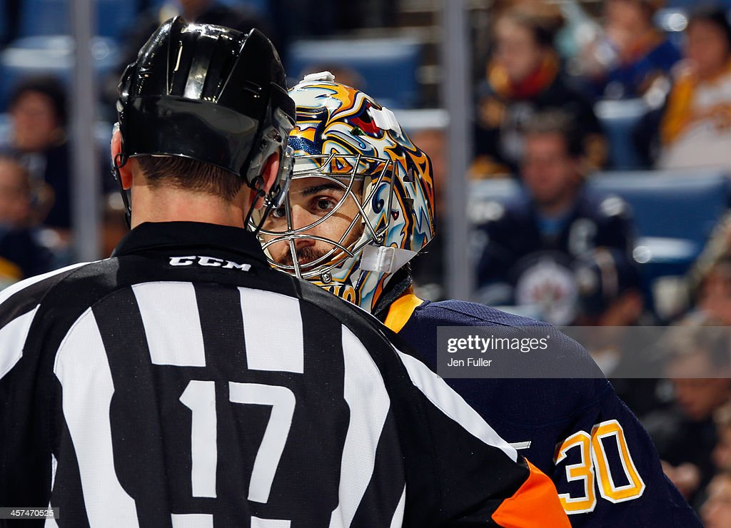 Ryan Miller #30 of the Buffalo Sabres talks with referee #17 Frederick L'Ecuyer during a game against the Winnipeg Jets at First Niagara Center on December 17, 2013 in Buffalo, New York. Buffalo defeated Winnipeg 4-2.