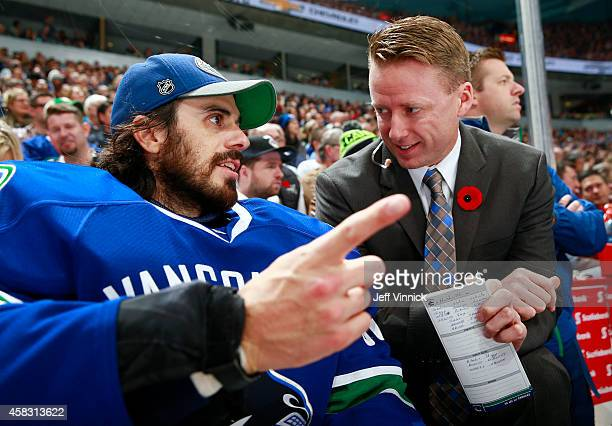 Ryan Miller of the Vancouver Canucks and Assistant coach assistant coach Glen Gulutzan talk on the bench during their NHL game against the Nashville...