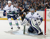 Ryan Miller of the Vancouver Canucks defends the net against the Buffalo Sabres alongside teammate Henrik Sedin and Mark Pysyk of Buffalo at First...