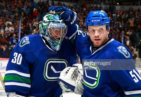 Ryan Miller of the Vancouver Canucks is congratulated by teammate Derek Dorsett during their NHL game against the Boston Bruins at Rogers Arena...