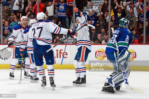 Ryan Miller of the Vancouver Canucks looks on as Iiro Pakarinen of the Edmonton Oilers is congratulated by Milan Lucic after scoring during their NHL...