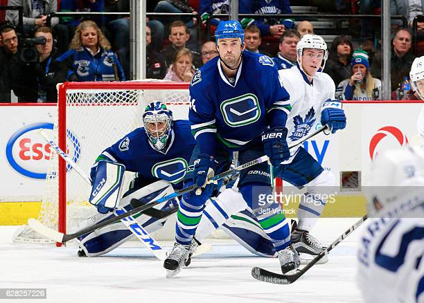 Ryan Miller of the Vancouver Canucks peeks around Tyler Bozak of the Toronto Maple Leafs and Erik Gudbranson of the Vancouver Canucks during their...