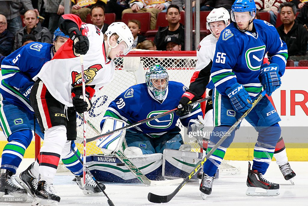 Ryan Miller #30 of the Vancouver Canucks peers through a crowd for the puck during their NHL game against the Ottawa Senators at Rogers Arena February 25, 2016 in Vancouver, British Columbia, Canada.