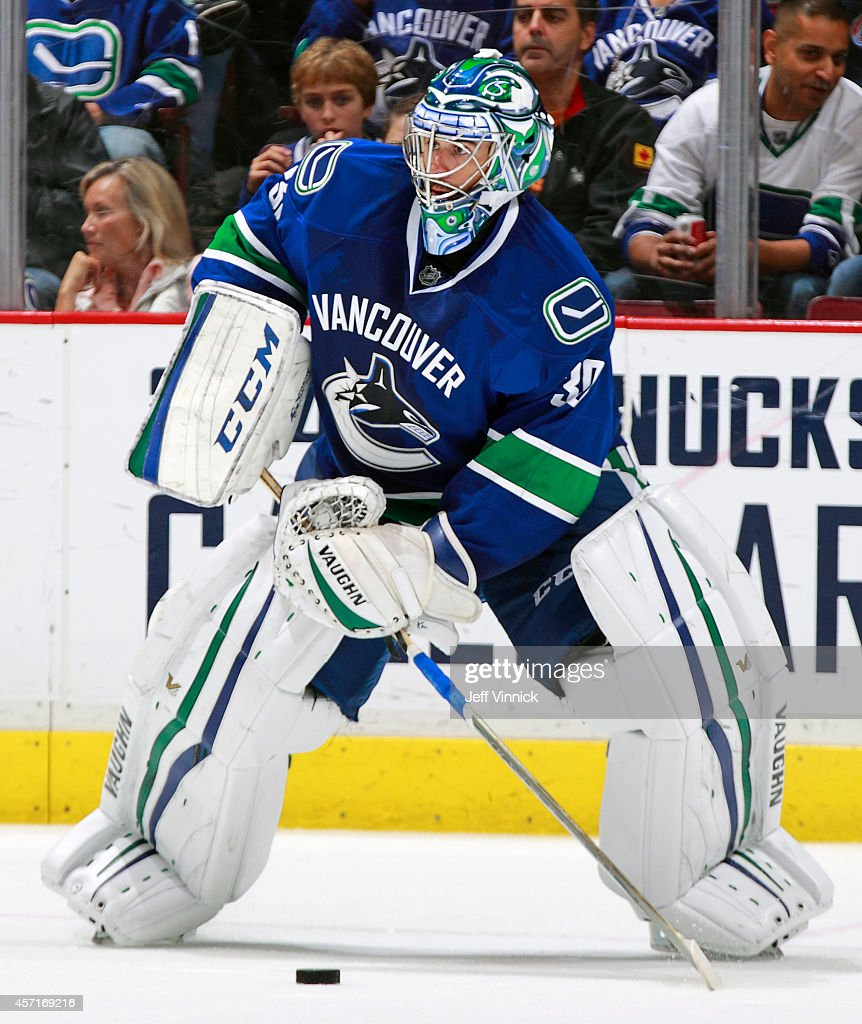 Ryan Miller of the Vancouver Canucks plays the puck during their NHL game against the Edmonton Oilers at Rogers Arena October 11 2014 in Vancouver...