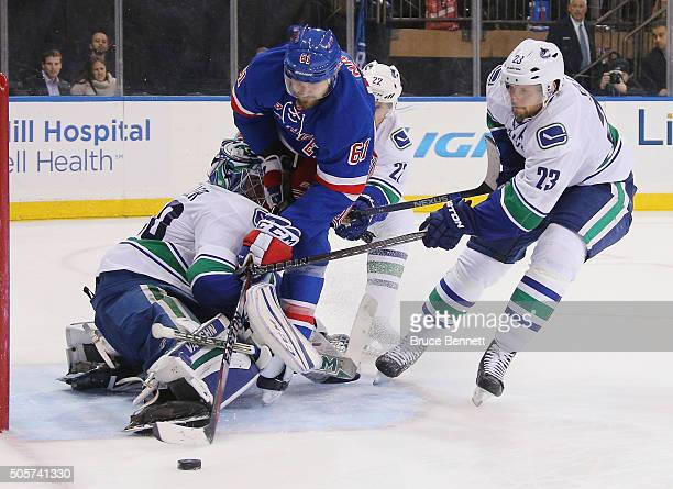 Ryan Miller of the Vancouver Canucks stops Rick Nash of the New York Rangers during the overtime period at Madison Square Garden on January 19 2016...