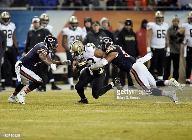 Ryan Mundy and Jon Bostic of the Chicago Bears tackle Mark Ingram of the New Orleans Saints during the second quarter at Soldier Field on December 15...