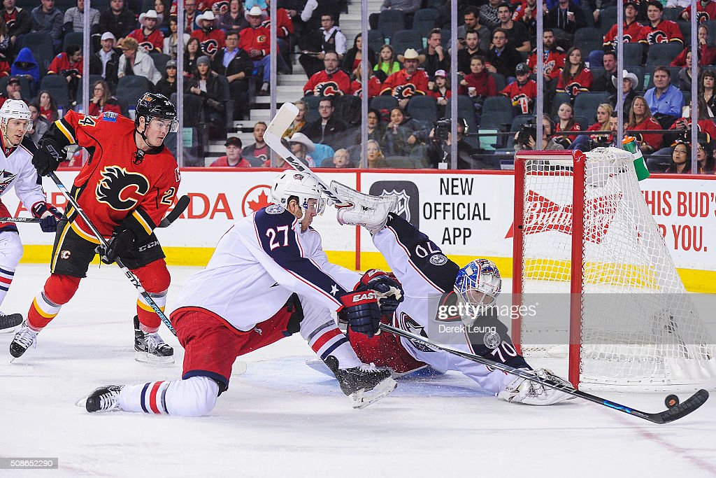 Ryan Murray #27 (L) and Joonas Korpisalo #70 of the Columbus Blue Jackets stop a shot from the Calgary Flames during an NHL game at Scotiabank Saddledome on February 5, 2016 in Calgary, Alberta, Canada.
