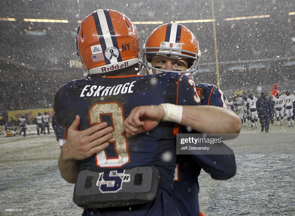 Ryan Nassib #12 and Durell Eskridge #3 of the Syracuse Orange celebrate victory over the West Virginia Mountaineers in the New Era Pinstripe Bowl at Yankee Stadium on December 29, 2012 in the Bronx borough of New York City.