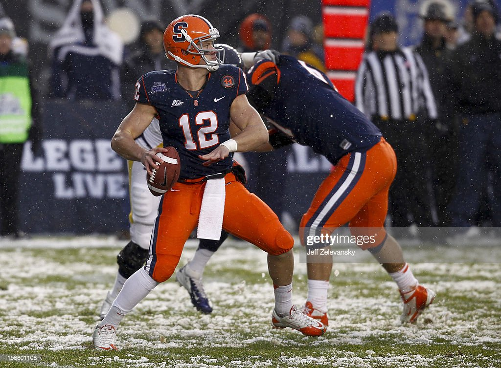 Ryan Nassib #12 of the Syracuse Orange drops back against the West Virginia Mountaineers in the New Era Pinstripe Bowl at Yankee Stadium on December 29, 2012 in the Bronx borough of New York City.
