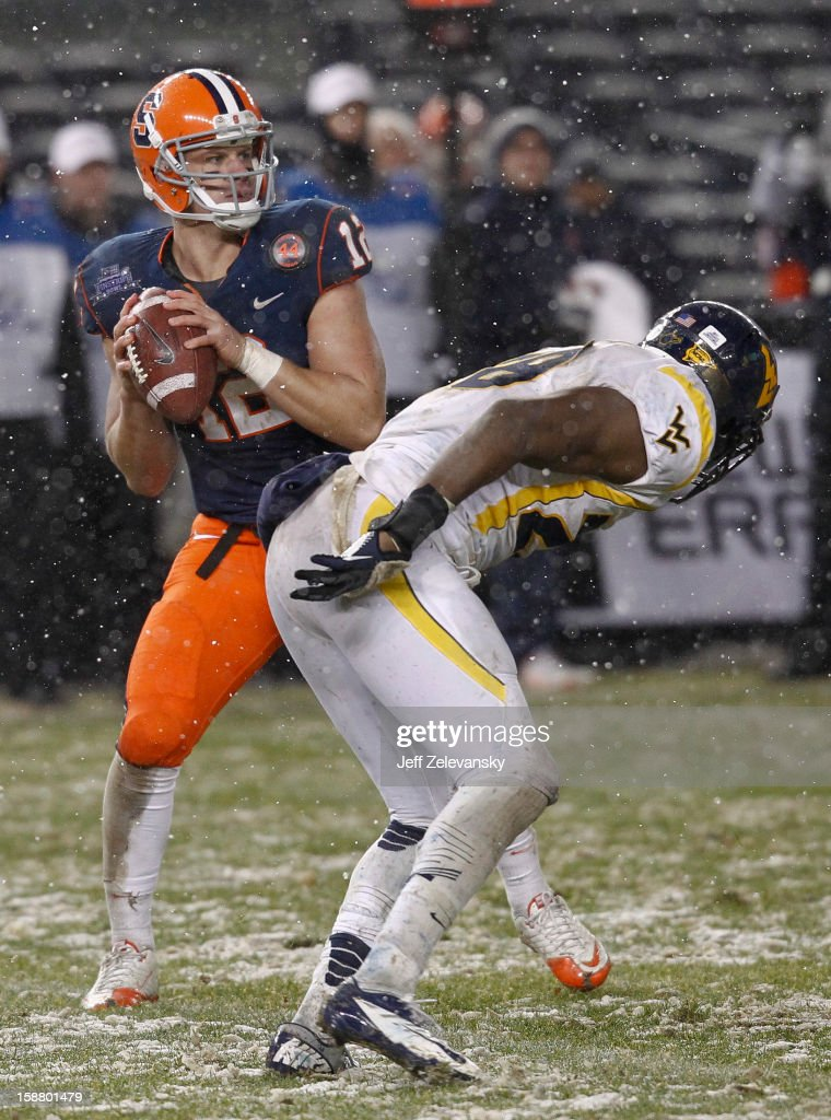 Ryan Nassib #12 of the Syracuse Orange looks for an open man against the West Virginia Mountaineers in the New Era Pinstripe Bowl at Yankee Stadium on December 29, 2012 in the Bronx borough of New York City.