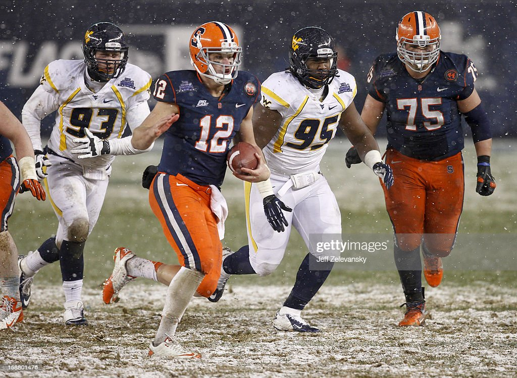 Ryan Nassib #12 of the Syracuse Orange scrambles in front of Christian Brown #95 of the West Virginia Mountaineers in the New Era Pinstripe Bowl at Yankee Stadium on December 29, 2012 in the Bronx borough of New York City.