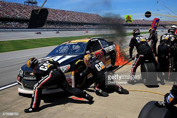 Ryan Newman driver of the Caterpillar Chevrolet catches fire on pit road during the NASCAR Sprint Cup Series GEICO 500 at Talladega Superspeedway on...