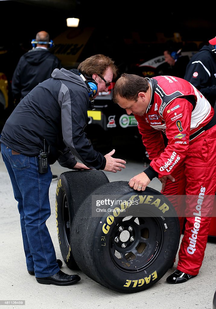 Ryan Newman driver of the Quicken Loans Chevrolet and team owner Richard Childress inspect tires from Newman's car during practice for the NASCAR...