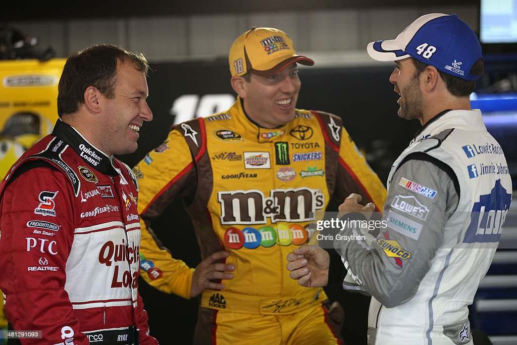Ryan Newman, driver of the #31 Quicken Loans Chevrolet, <a gi-track='captionPersonalityLinkClicked' href=/galleries/search?phrase=Kyle+Busch&family=editorial&specificpeople=211123 ng-click='$event.stopPropagation()'>Kyle Busch</a>, driver of the #18 M&M's Toyota, and Jimmie Johnson, driver of the #48 Lowe's Chevrolet, talk in the garage during a rain delay in practice for the NASCAR Sprint Cup Series STP 500 at Martinsville Speedway on March 29, 2014 in Martinsville, Virginia.