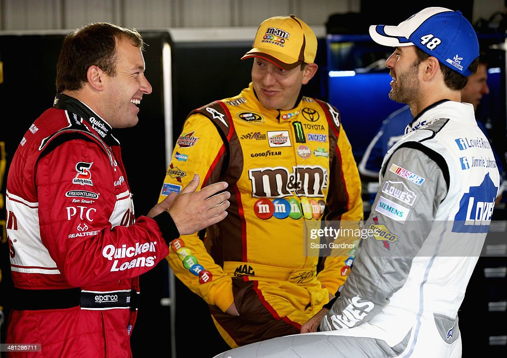Ryan Newman, driver of the #31 Quicken Loans Chevrolet, talks with <a gi-track='captionPersonalityLinkClicked' href=/galleries/search?phrase=Kyle+Busch&family=editorial&specificpeople=211123 ng-click='$event.stopPropagation()'>Kyle Busch</a>, driver of the #18 M&M's Toyota, and Jimmie Johnson, driver of the #48 Lowe's Chevrolet, in the garage area during a rain delay in practice for the NASCAR Sprint Cup Series STP 500 at Martinsville Speedway on March 29, 2014 in Martinsville, Virginia.