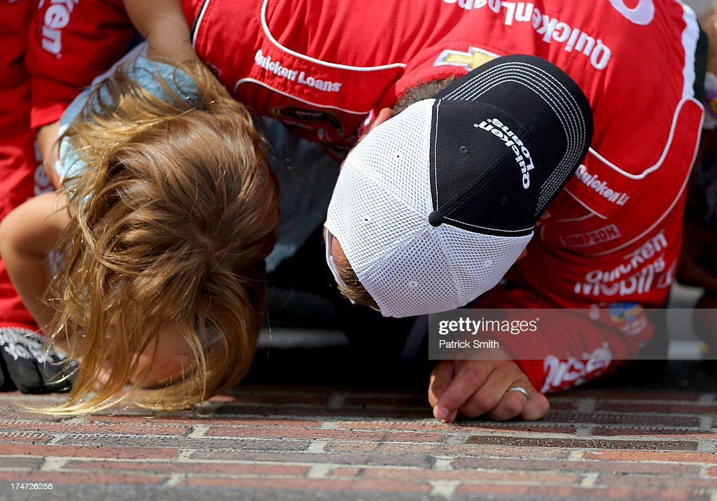 Ryan Newman, driver of the #39 Quicken Loans/The Smurfs Chevrolet, and his daughter Brooklyn Sage kiss the bricks after winning the NASCAR Sprint Cup Series Samuel Deeds 400 At The Brickyard at Indianapolis Motor Speedway on July 28, 2013 in Indianapolis, Indiana.