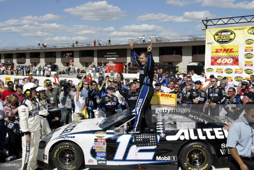 Ryan Newman stands on his car with his team around him after his victory in the NASCAR Nextel Cup DHL 400 at Michigan International Speedway in...