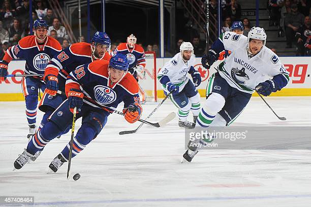 Ryan NugentHopkins and Benoit Pouliot of the Edmonton Oilers skate into the offensive zone while being chased by Alexander Edler of the Vancouver...