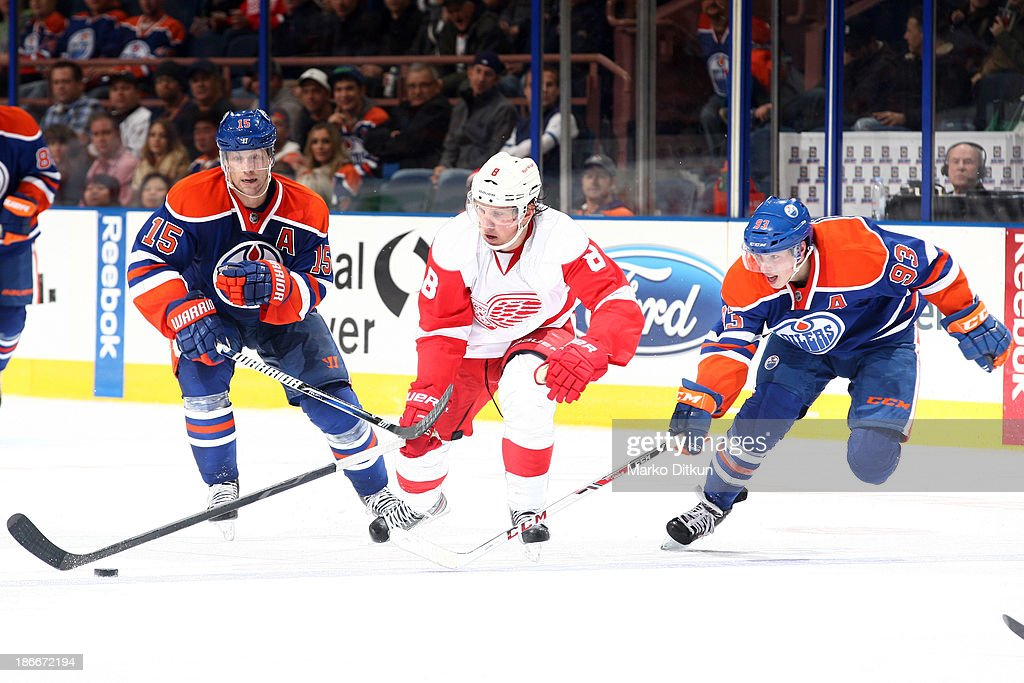 <a gi-track='captionPersonalityLinkClicked' href=/galleries/search?phrase=Ryan+Nugent-Hopkins&family=editorial&specificpeople=7144190 ng-click='$event.stopPropagation()'>Ryan Nugent-Hopkins</a> #93 and <a gi-track='captionPersonalityLinkClicked' href=/galleries/search?phrase=Nick+Schultz&family=editorial&specificpeople=203252 ng-click='$event.stopPropagation()'>Nick Schultz</a> #15 of the Edmonton Oilers chase <a gi-track='captionPersonalityLinkClicked' href=/galleries/search?phrase=Justin+Abdelkader&family=editorial&specificpeople=2271858 ng-click='$event.stopPropagation()'>Justin Abdelkader</a> #8 of the Detroit Red Wings on November 2, 2013 at Rexall Place in Edmonton, Alberta, Canada.