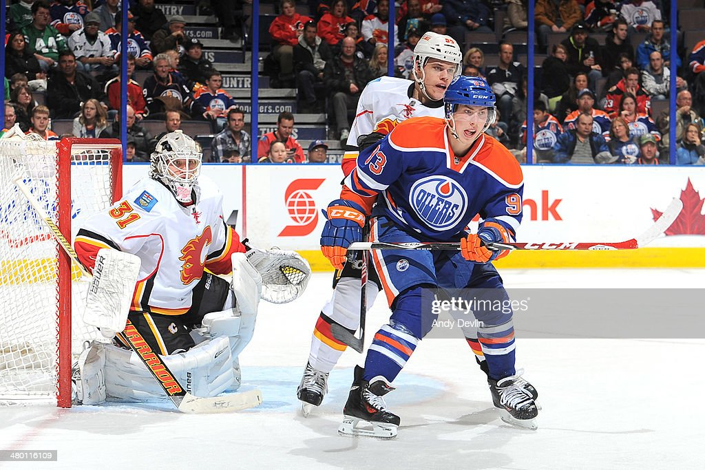 <a gi-track='captionPersonalityLinkClicked' href=/galleries/search?phrase=Ryan+Nugent-Hopkins&family=editorial&specificpeople=7144190 ng-click='$event.stopPropagation()'>Ryan Nugent-Hopkins</a> #93 of the Edmonton Oilers battles for position against Tyler Wotherspoon #56 of the Calgary Flames on March 22, 2014 at Rexall Place in Edmonton, Alberta, Canada.