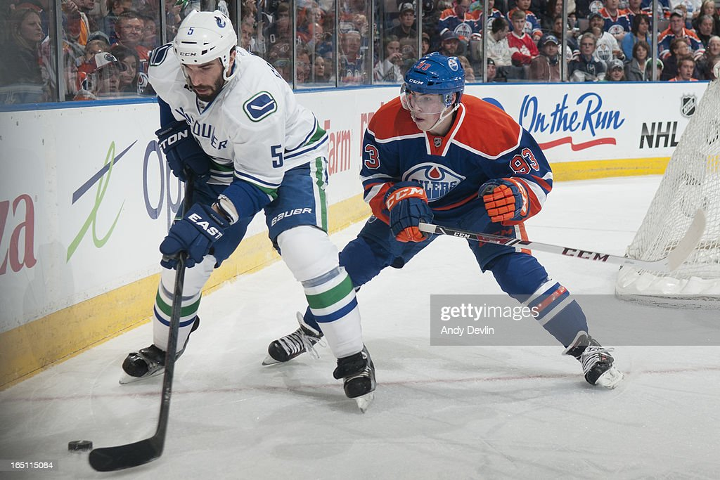 <a gi-track='captionPersonalityLinkClicked' href=/galleries/search?phrase=Ryan+Nugent-Hopkins&family=editorial&specificpeople=7144190 ng-click='$event.stopPropagation()'>Ryan Nugent-Hopkins</a> #93 of the Edmonton Oilers battles for the puck against <a gi-track='captionPersonalityLinkClicked' href=/galleries/search?phrase=Jason+Garrison&family=editorial&specificpeople=2143635 ng-click='$event.stopPropagation()'>Jason Garrison</a> #5 of the Vancouver Canucks on March 30, 2013 at Rexall Place in Edmonton, Alberta, Canada.