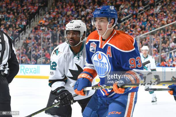 Ryan NugentHopkins of the Edmonton Oilers battles for the puck against Joel Ward of the San Jose Sharks on March 30 2017 at Rogers Place in Edmonton...