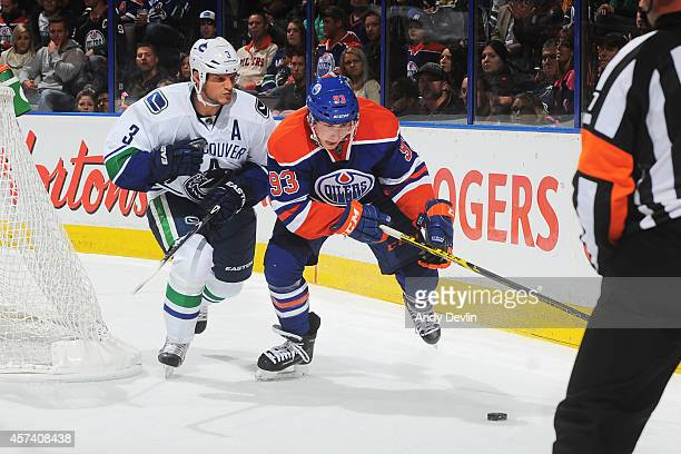 Ryan NugentHopkins of the Edmonton Oilers battles for the puck against Kevin Bieksa of the Vancouver Canucks on October 17 2014 at Rexall Place in...